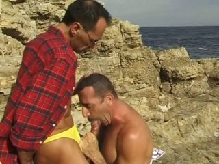 Middle aged uncaring guys sucking each time other in the beach